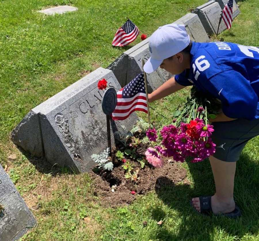 young boy putting flowers on Veterans graves