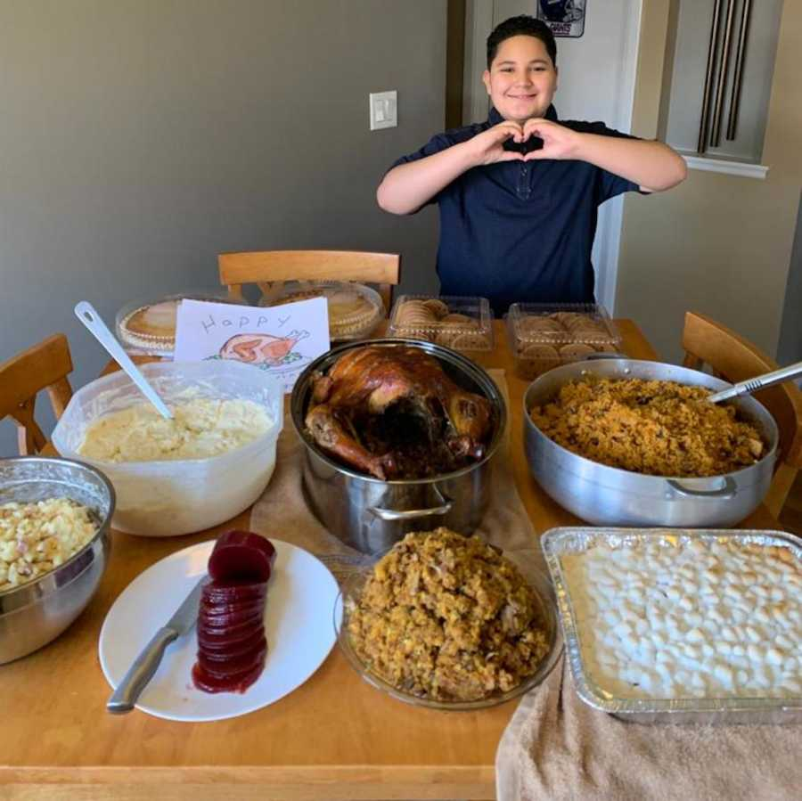 young boy with Thanksgiving dinner on table