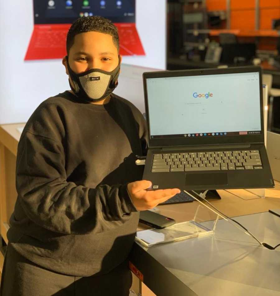 young boy holding laptop