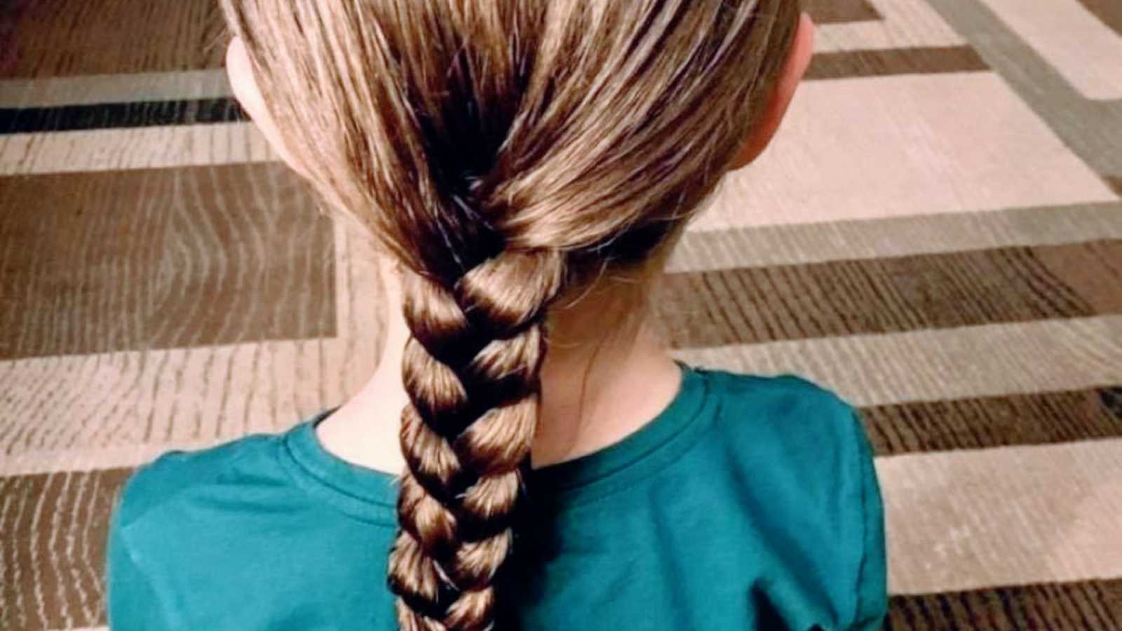 Little girl sits on the floor and shows off her freshly braided hair