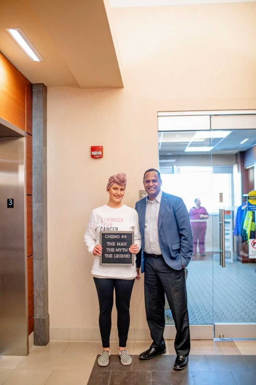 """Woman with triple negative breast cancer takes a photo with her doctor with a sign that reads """"the man, the myth, the legend"""""""