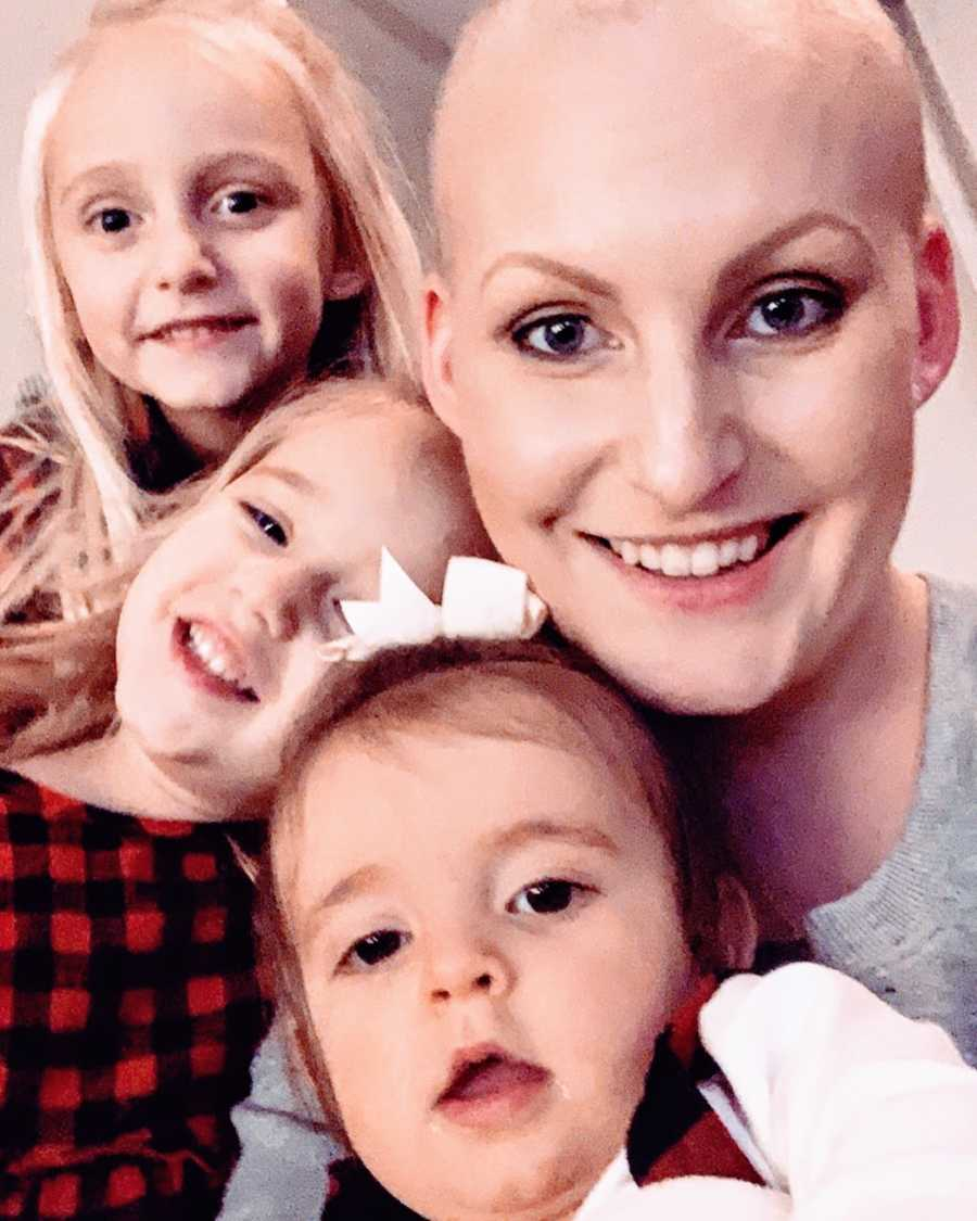 Woman with triple negative breast cancer takes a smiling selfie with her three daughters