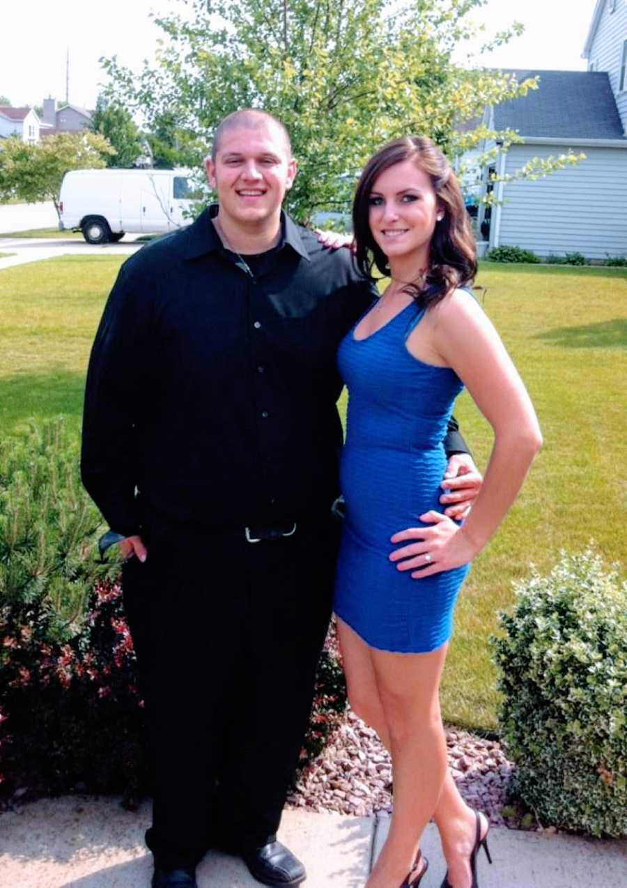 Young couple pose in a black suit and blue dress before going to a formal event