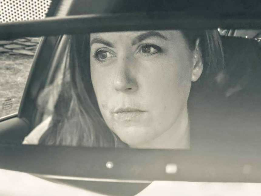 Woman takes a moody selfie in the rearview mirror of her car while reflecting on her inner self