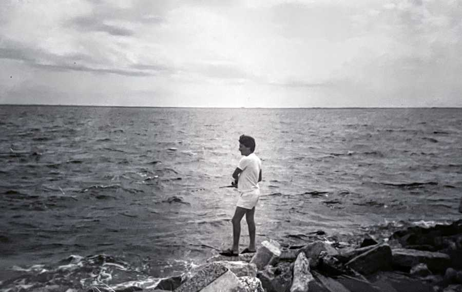 Black and white photo of a man fishing in the ocean while standing on rocks