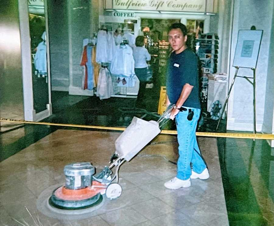 A man uses a machine to buff the floor at his work