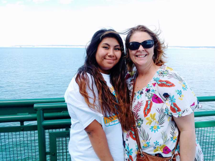 Woman poses with her adopted daughter by the water