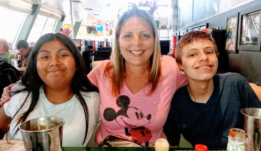 Mom of two adopted children takes a photo with them in Disney