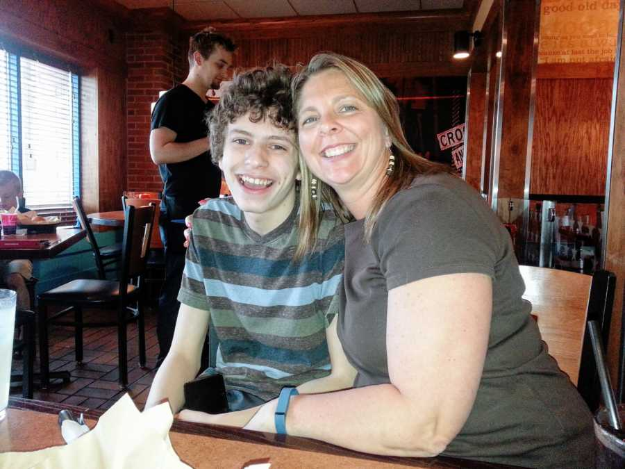 Mom takes a photo with her adopted autistic son in a restaurant