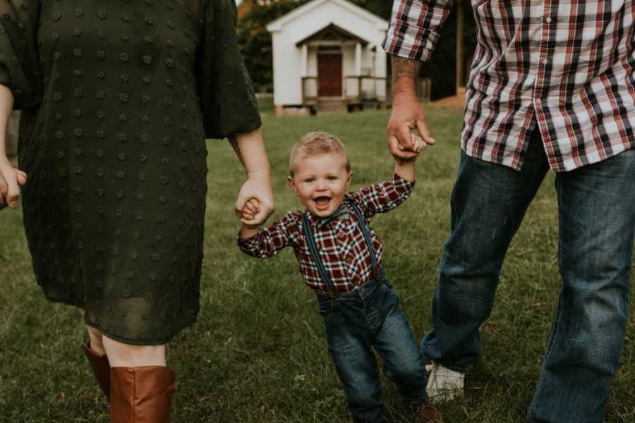 Parents take a photo with their son skipping and smiling and holding their hands after adopting him