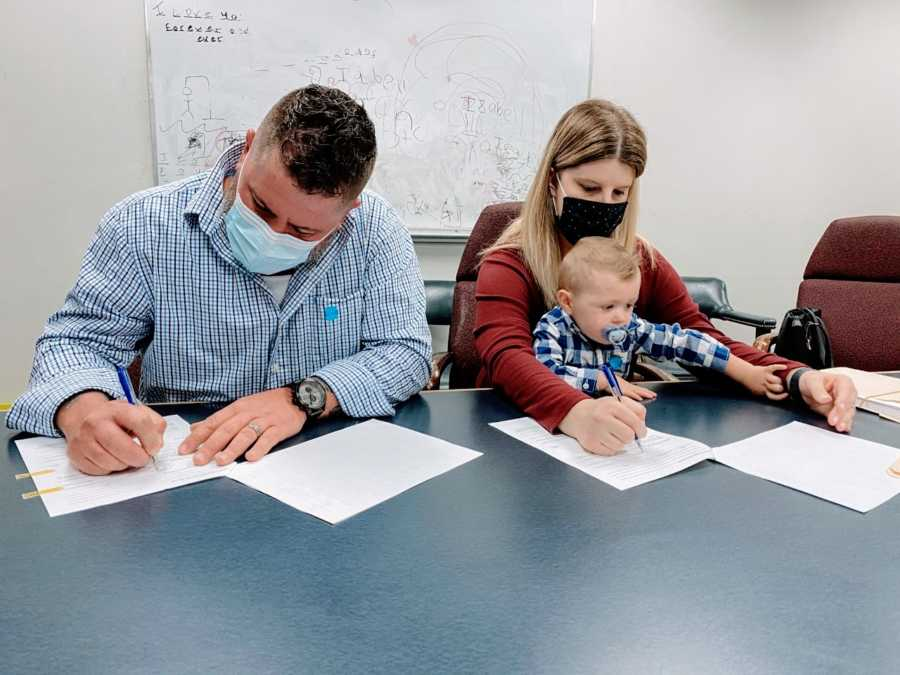 Foster parents sign paperwork to adopt the little boy they had been fostering
