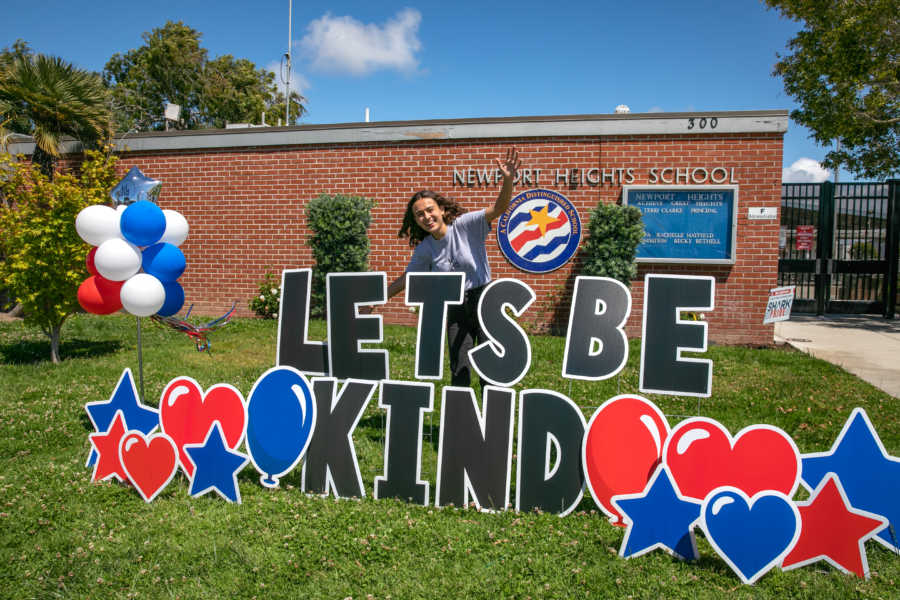 girl with let's be kind lawn sign