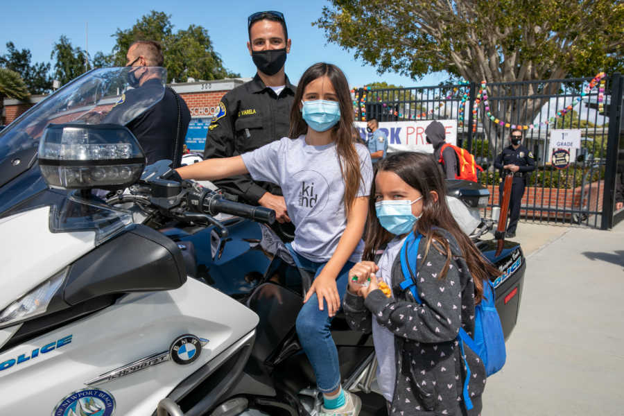 Masked girls with police officer and motorcycle