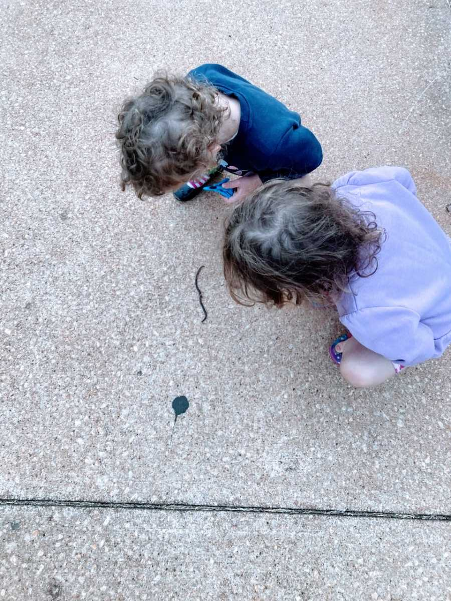 Mom snaps photo of her twins crouched down on the ground, watching a worm