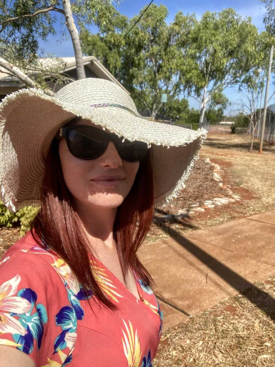 Mom takes a selfie in a sun hat during her nature walk with her children