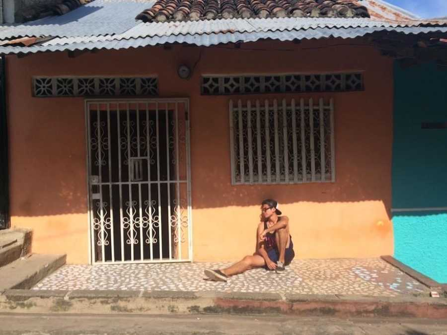 Man posing in front of house