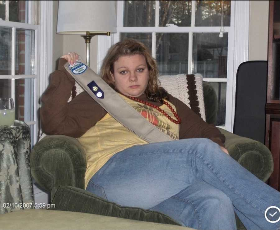 young girl sitting in chair holding sash
