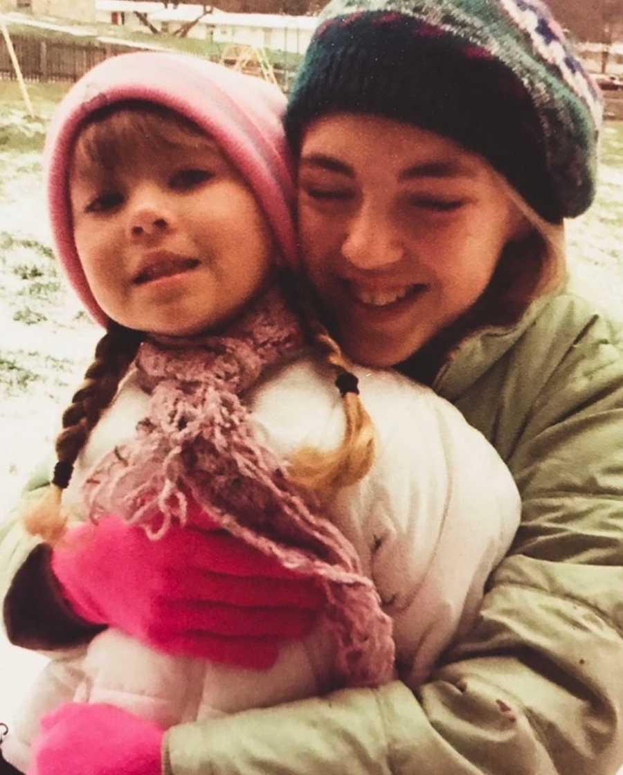 Girl hugging little sister