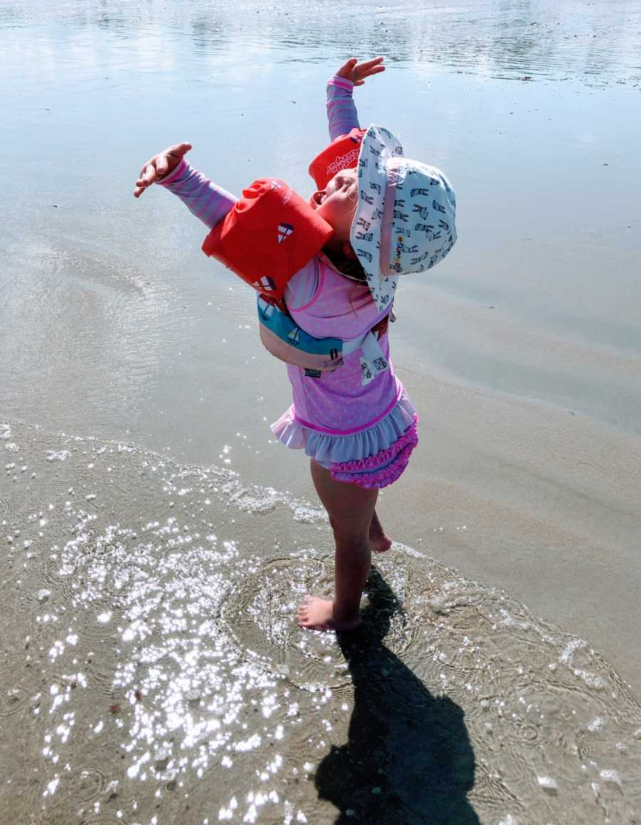 Little girl with Down syndrome dances around and relishes the sunshine while at the beach