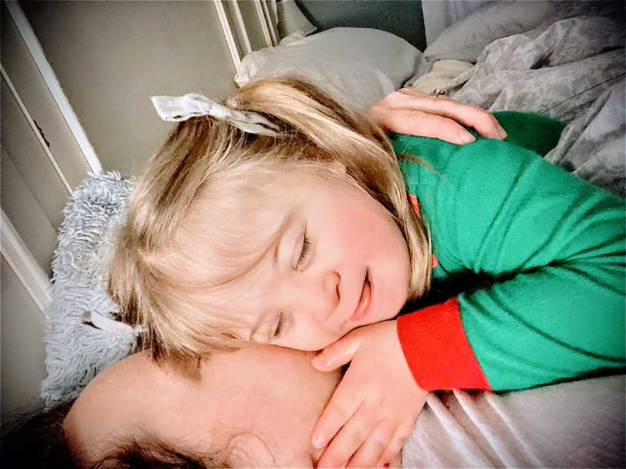 Little girl with Down syndrome smiles and cuddles with her dad at Christmastime