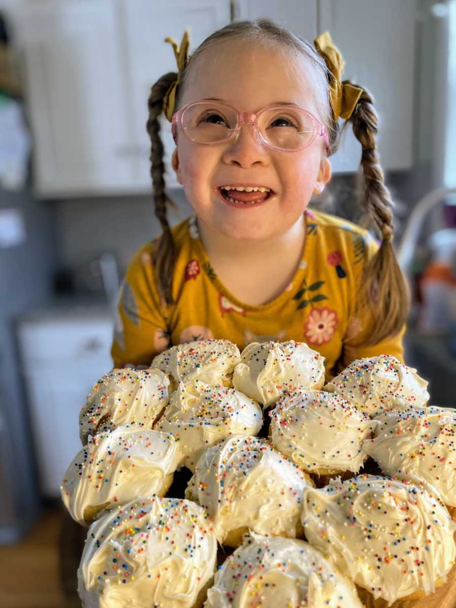 Girl with Down syndrome smiles in front a batch of freshly baked vanilla cupcakes