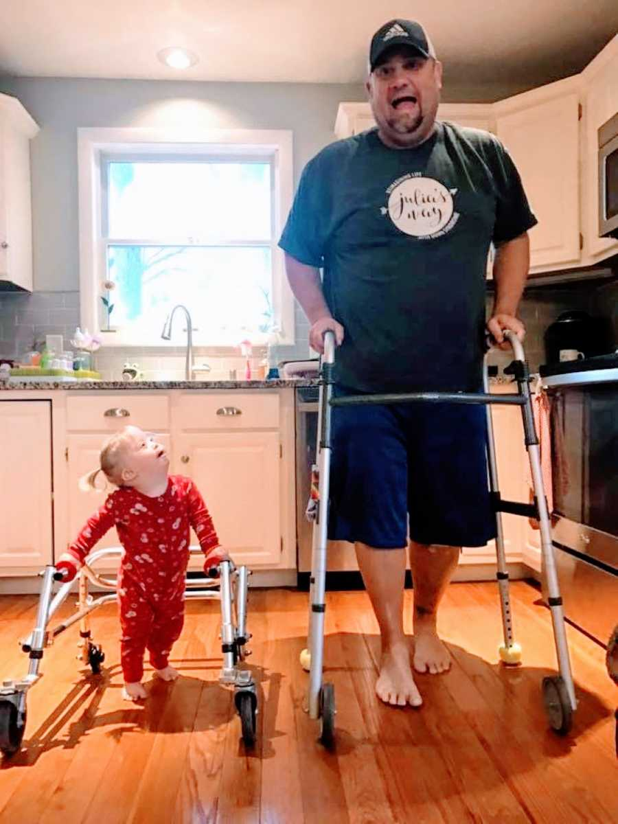 Little girl with Down syndrome practices walking with a walker with her dad's support