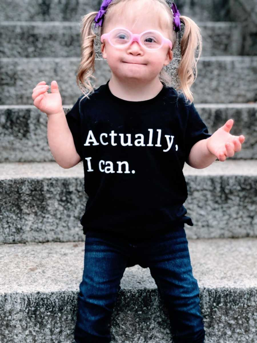 """Little girl with pink glasses and purple bows in her hair wears a t-shirt that says """"Actually, I can."""""""