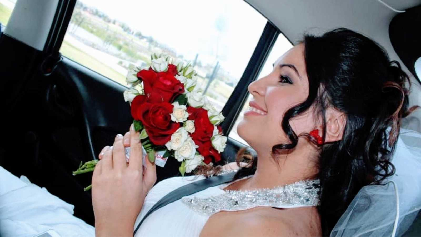 Beautiful young woman smiles on her wedding day with a red and white bouquet