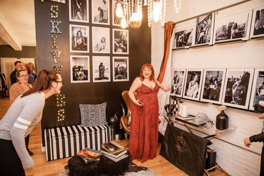 Woman wearing red dress pointing to photographs she took surrounded by friends