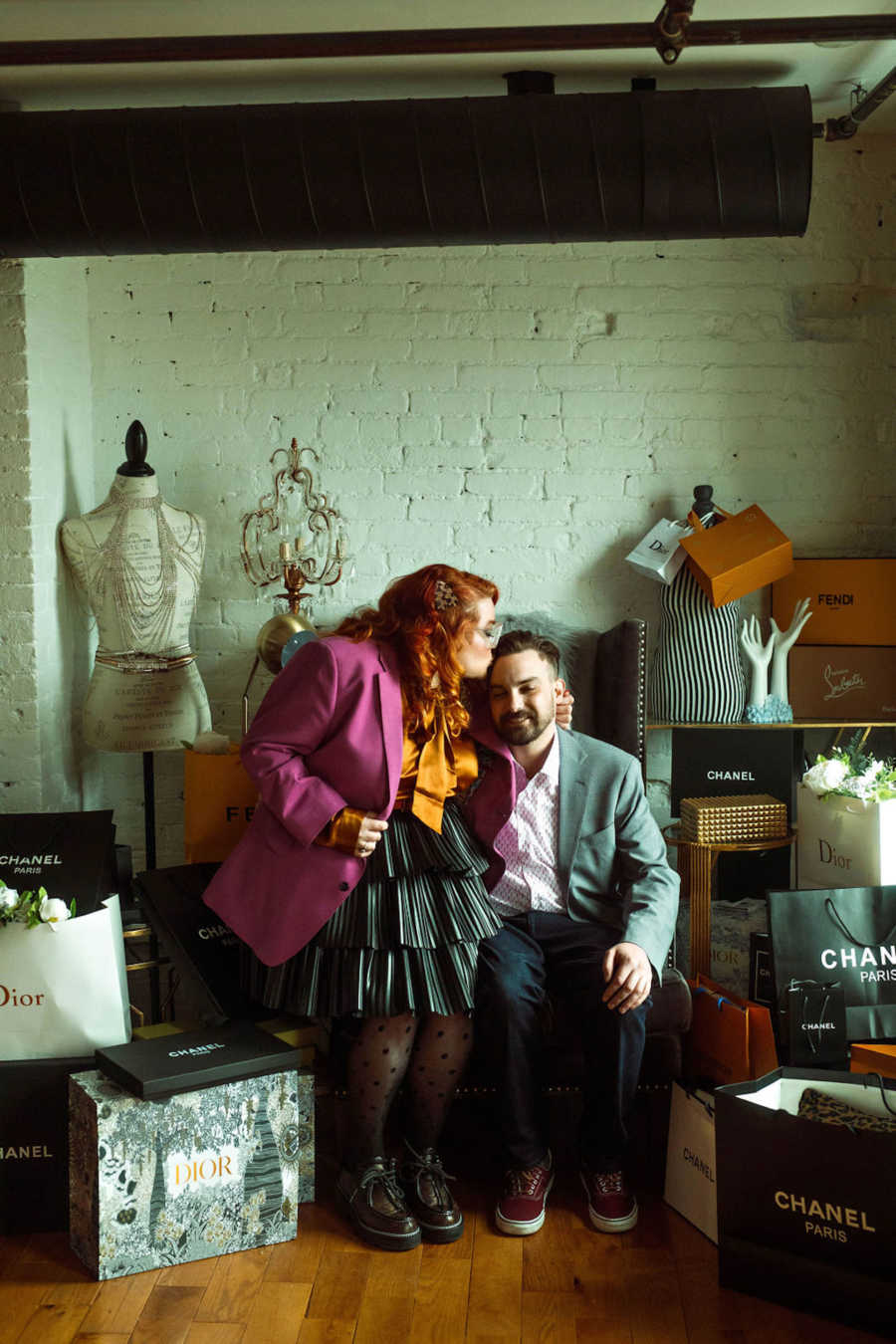Woman and man sitting in chair surrounded by shopping bags with the woman kissing the man on the head