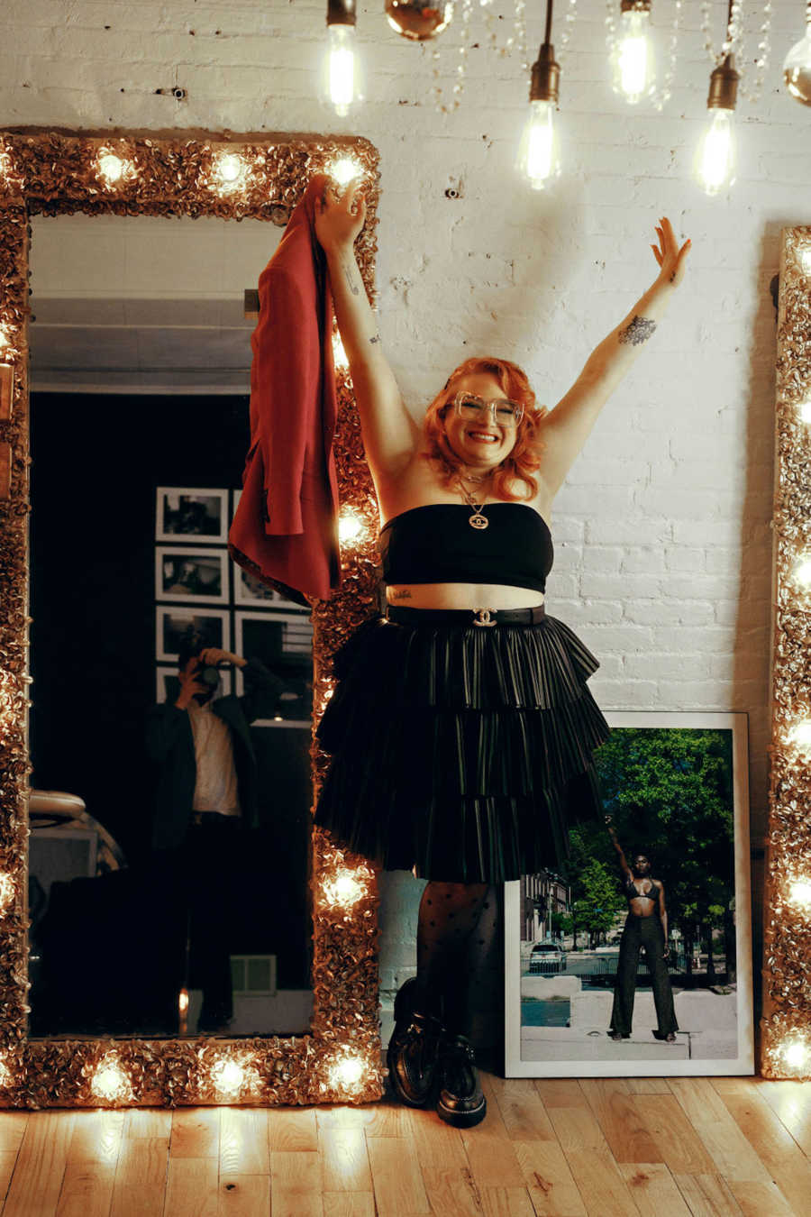 Woman wearing black crop top and black skirt holding arms above head in front of lighted mirror and white brick wall