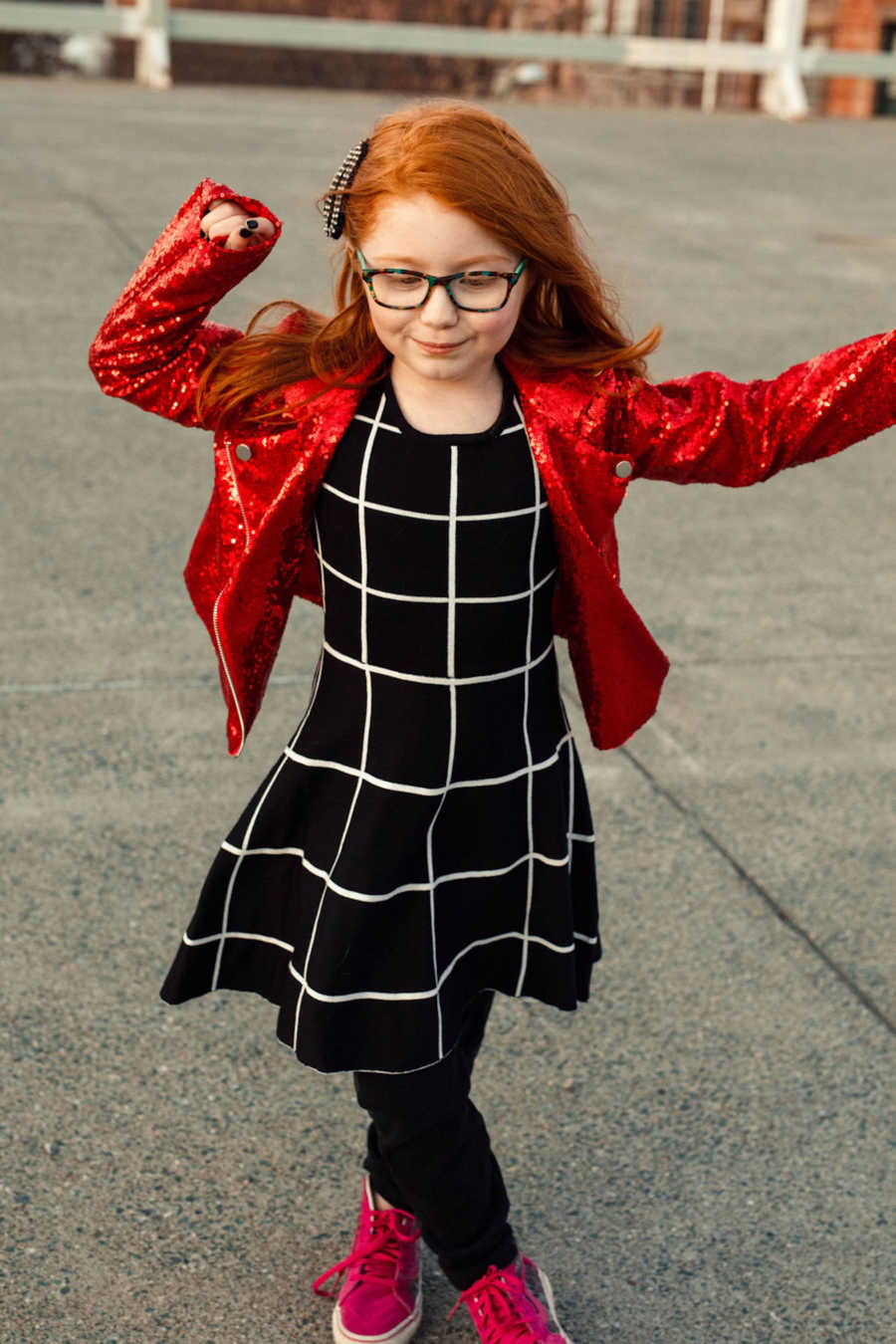 Young redhead girl wearing black grid dress and sparkly red jacket twirling outside