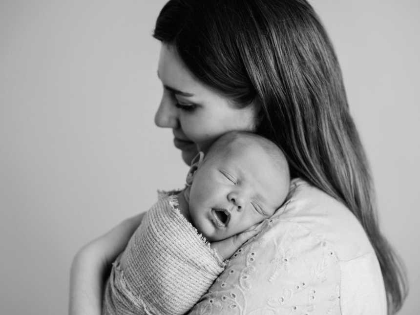 First time mom snuggles her sleeping newborn son during a photoshoot