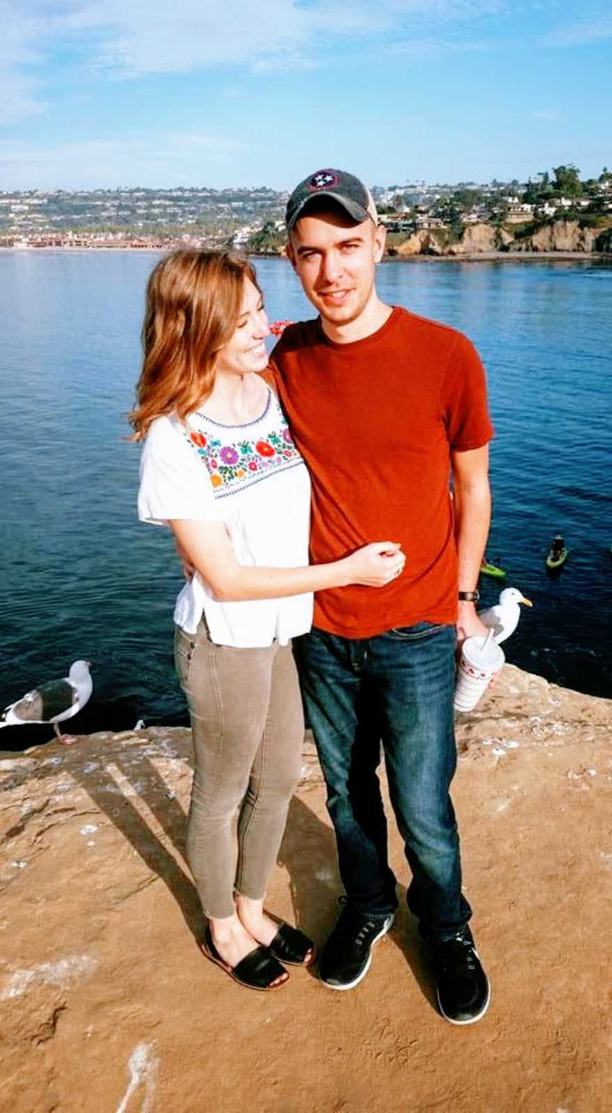 Couple take photo together while standing on a rock near the water with seagulls behind them