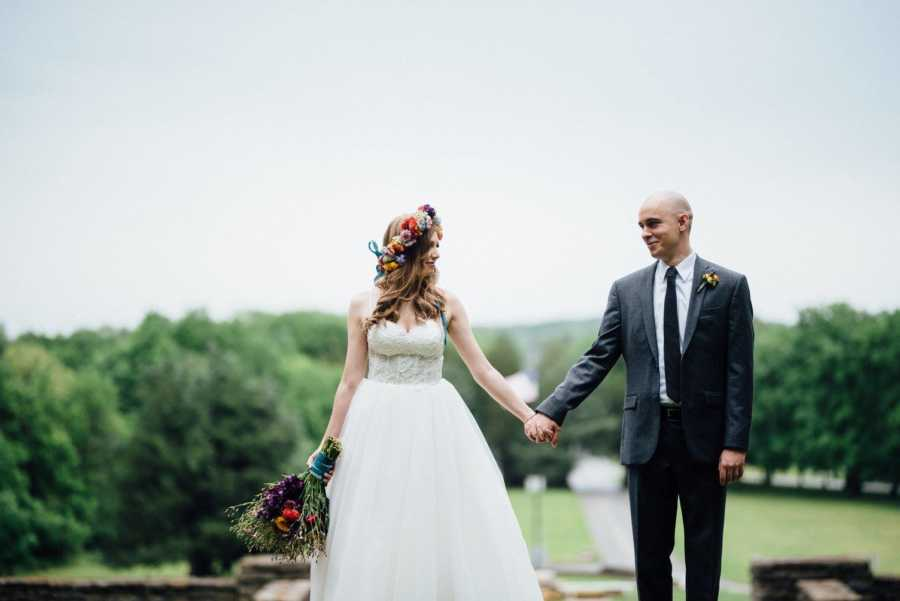 Newly weds smile at each other while they hold hands in their wedding day outfits