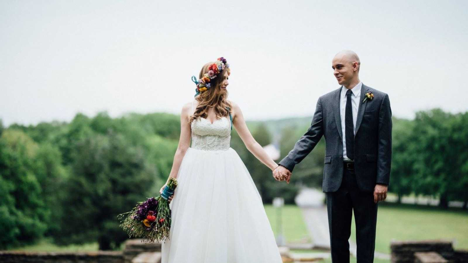 Couple hold hands and smile at each other during their wedding photoshoot