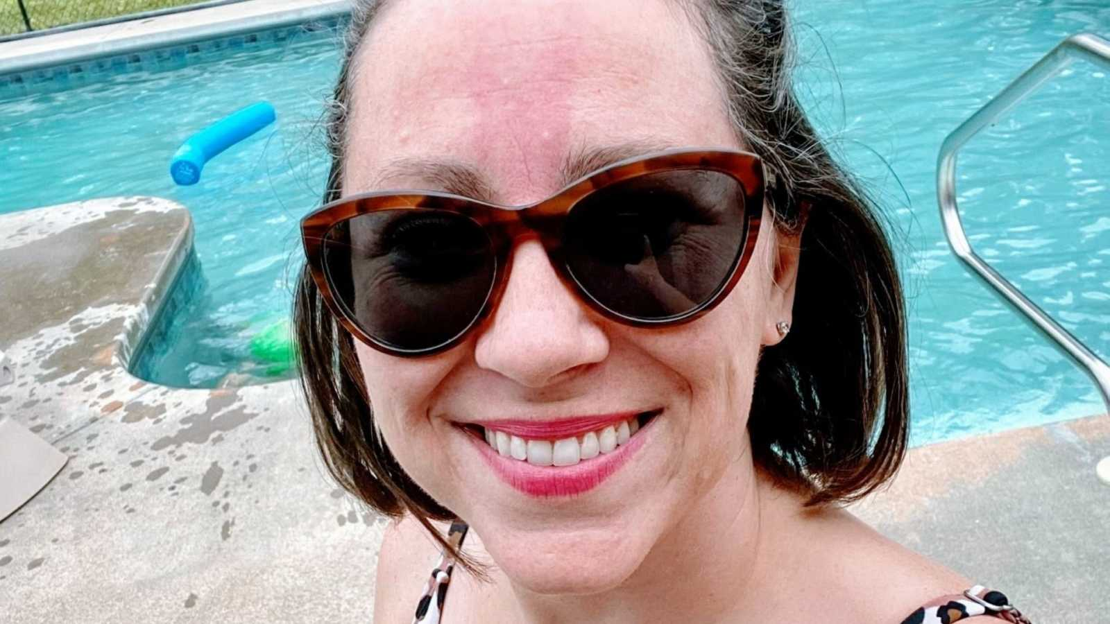 Woman in sunglasses takes a bikini selfie by the pool