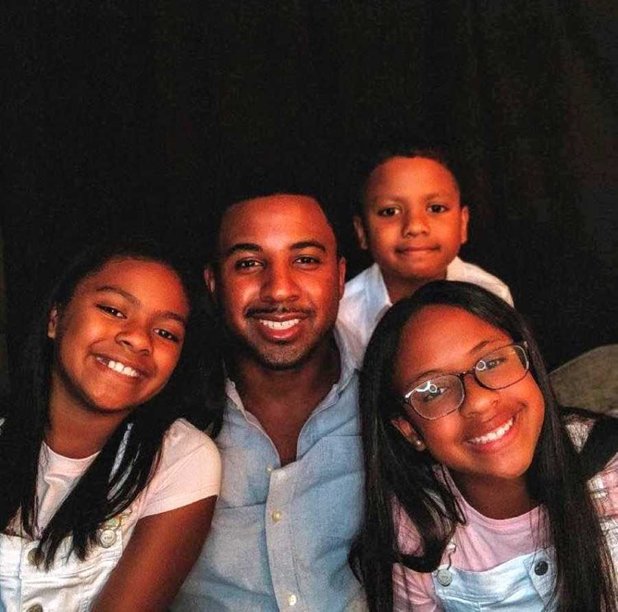 Single black dad poses for a family photo with his three kids