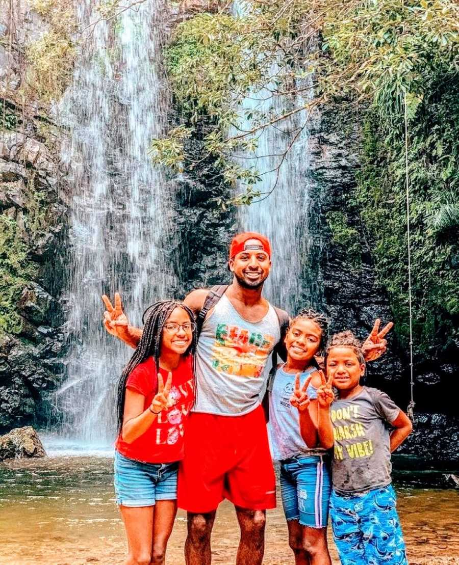 Single black dad takes three kids on a hike and pose for a photo in front of a waterfall