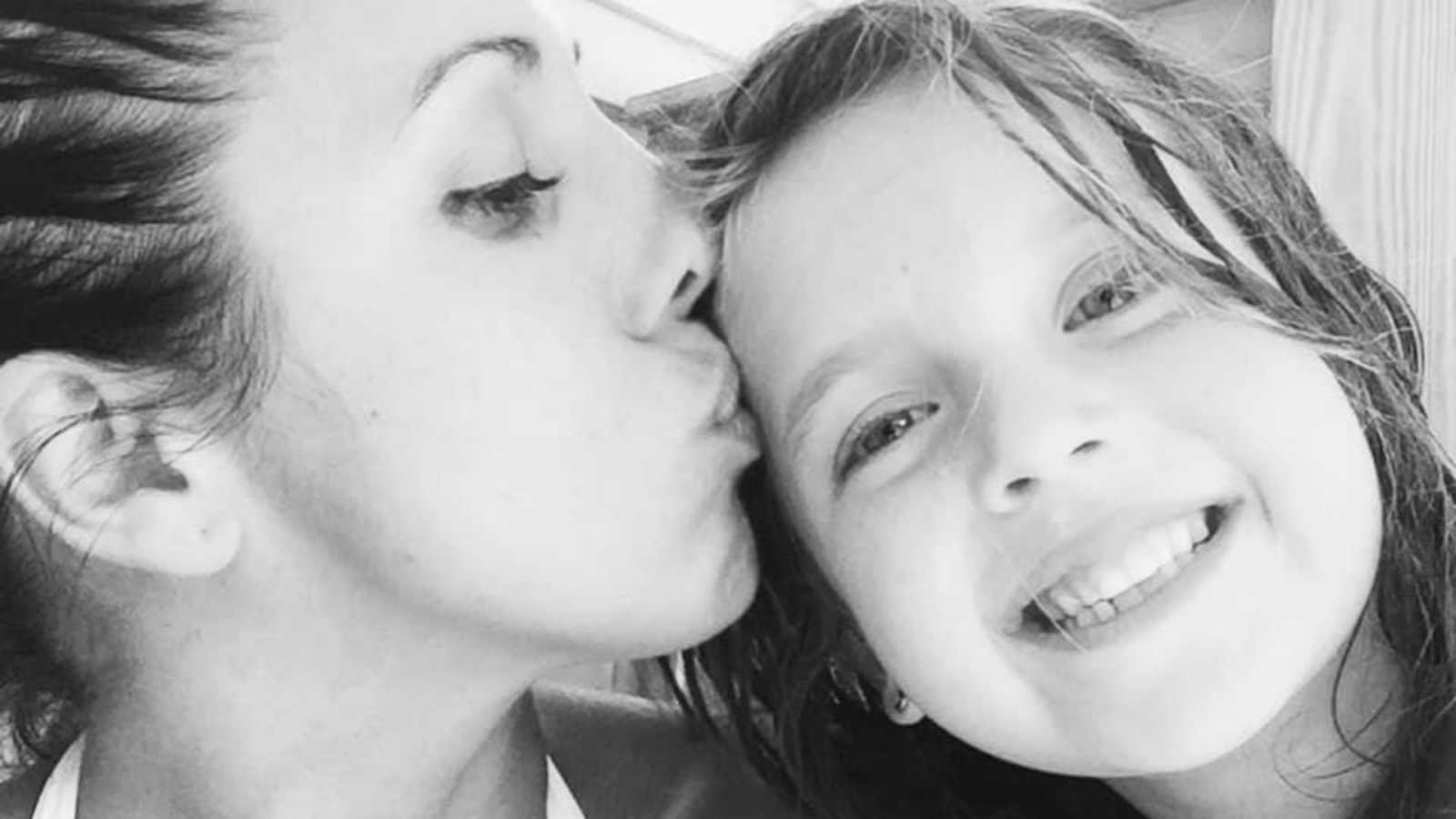 Mom kisses her daughter's forehead while she smiles