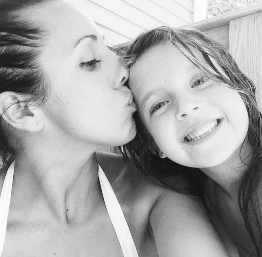 Mom takes a selfie with her daughter while kissing her forehead