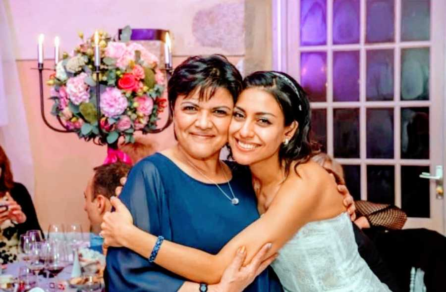 Bride takes a smiling photo with her mom during her wedding