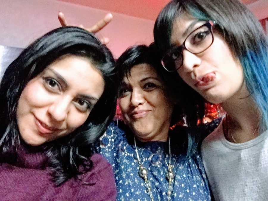 Pregnant woman takes a silly selfie with her mom and younger sister