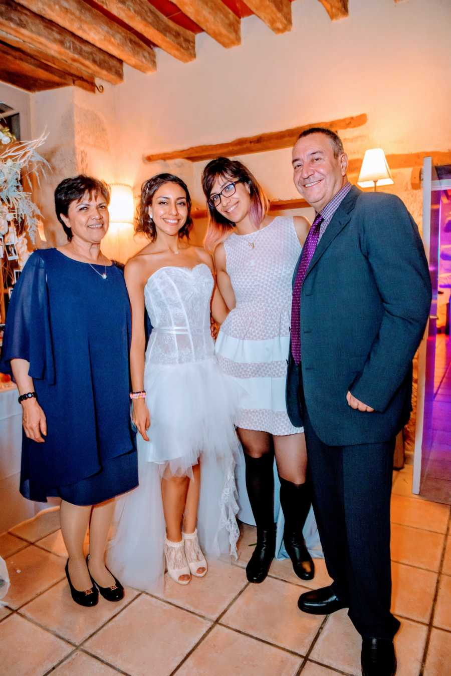 Woman takes a family photo with her parents and younger sister at her wedding reception