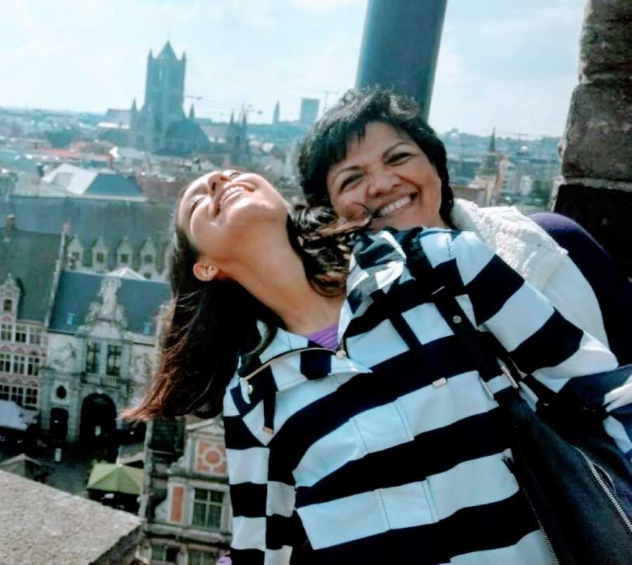 Woman laughs and smiles with her mom while sightseeing during their vacation