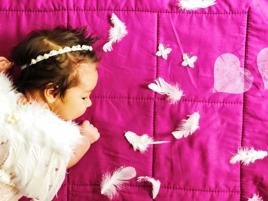 Mom snaps photo of newborn daughter laying on a pink blanket while dressed up as angel