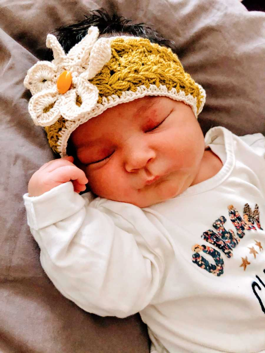 New mom snaps a photo of her newborn baby girl with a crocheted flower headband on