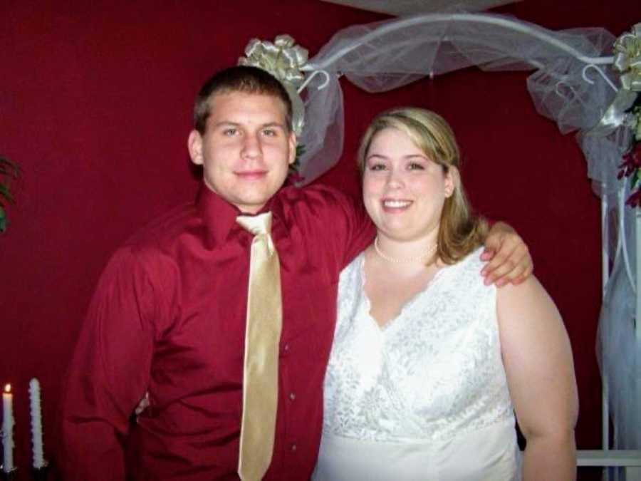 Couple take a photo together on their wedding day, groom in a red shirt and gold tie, bride in a size 24 white dress