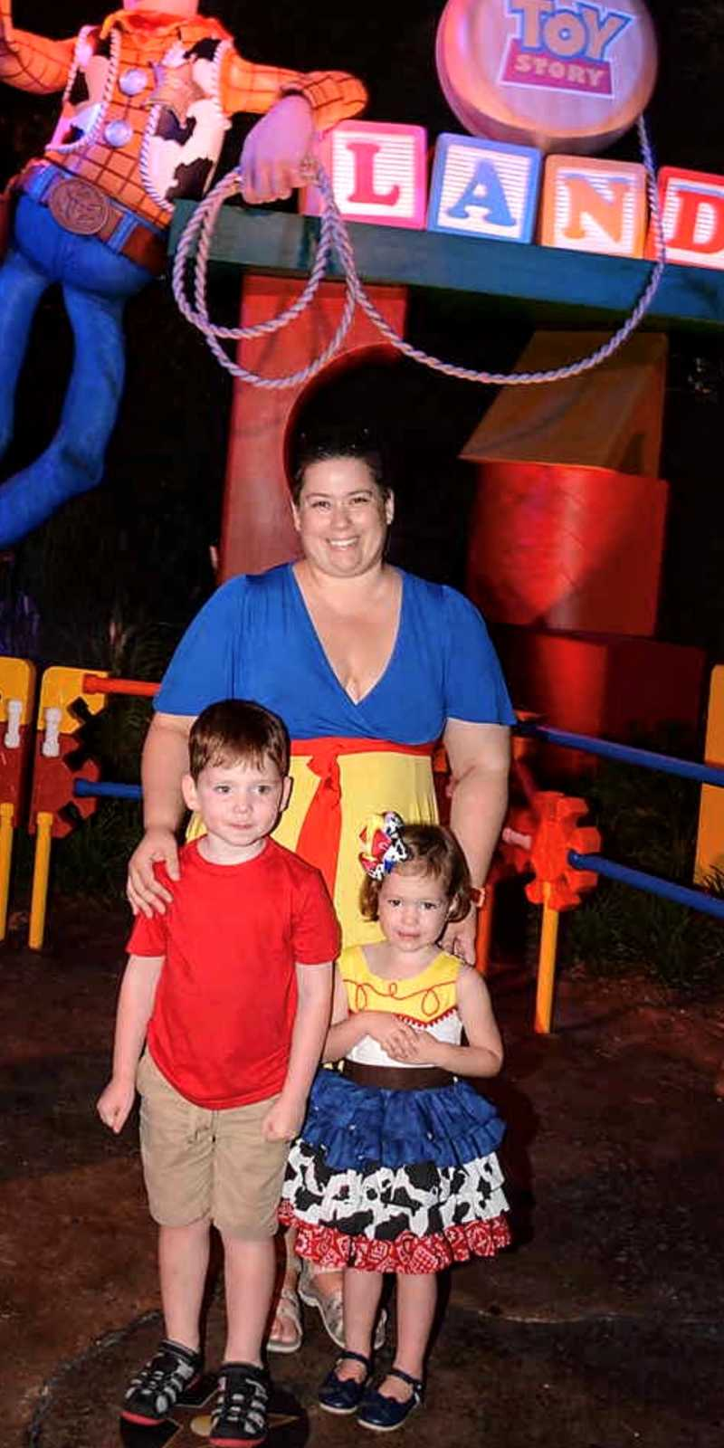 Mom takes a photo with two of her kids in Toy Story Land in Disney while her daughter is dressed up like Jessie