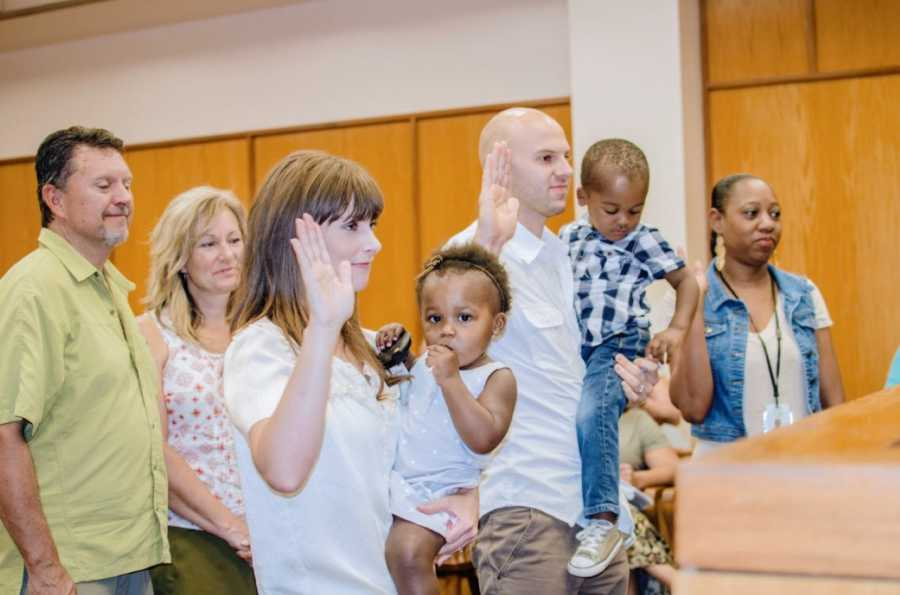 Couple take an oath in front of a judge while officially adopting their children